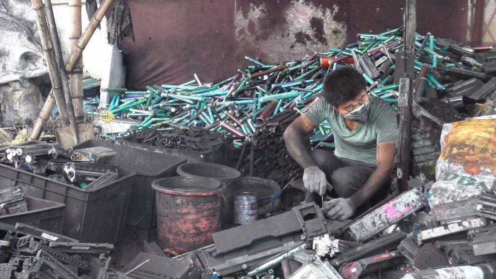 Worker dismantling toner cartridges - Guiyu, China - BaselActionNetwork